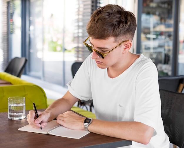 Uomo con occhiali da sole scrivendo al pub