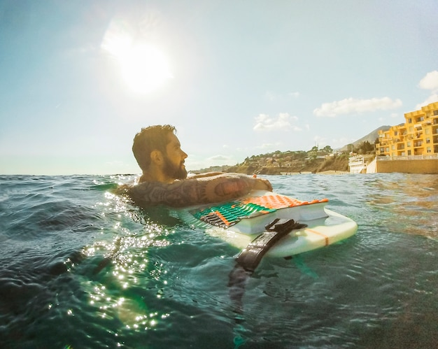 Man with surfboard in blue water