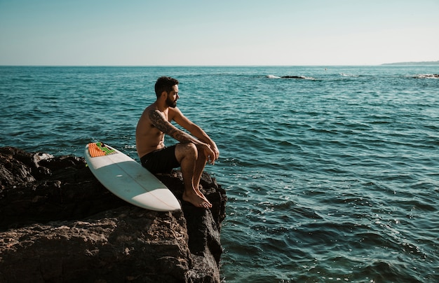 Man with surfboard relaxing on stone near sea