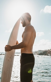 Man with surfboard standing against bright sky