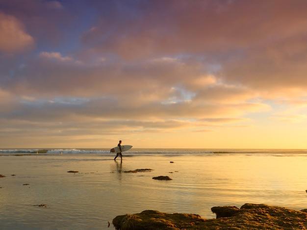 美しい夕日と海でサーフィンボードを持つ男