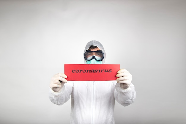 Man with surgical mask, glasses, white protective suit and red placard isolated in studio on white background. new pandemic epidemic new fast-spreading coronavirus.
