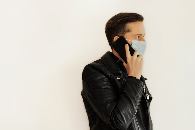 Man with surgical medical mask using cell phone.