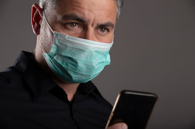 Man with surgical protection mask with worried face after watching news on mobile on gray background. coronavirus concept. protect your health.