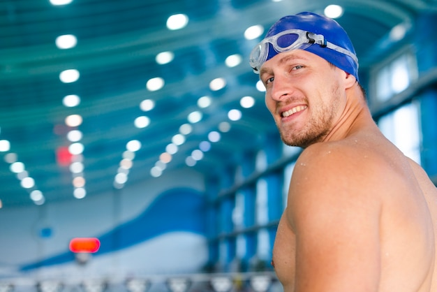 Man with swimming goggles looking at photographer