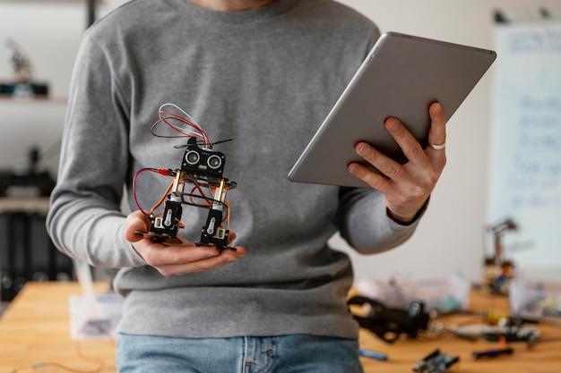 Человек с планшетом учится делать робота крупным планом
