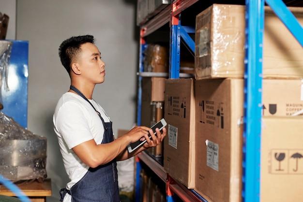 Человек с планшетного пк на складе