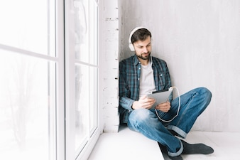 Man with tablet relaxing near window