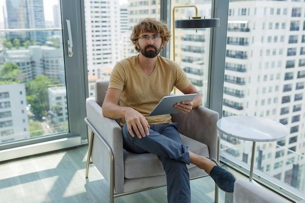 近代的なオフィスのソファーに座っているタブレットを持つ男。