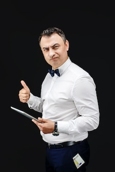 Man with tablet and thumb up. money sticking out of his pocket