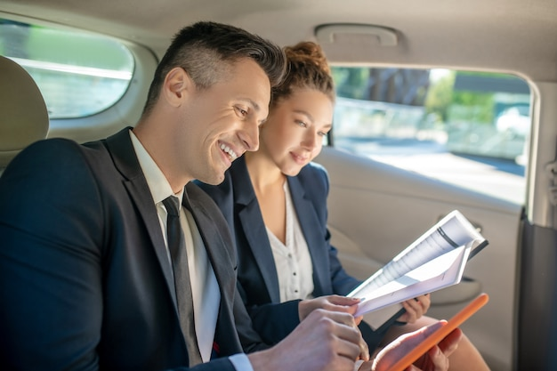 Man with tablet and woman discussing business in car.