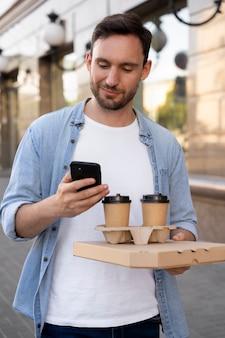 スマートフォンを使用して路上で持ち帰り用の食べ物を持つ男