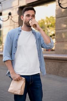 路上で持ち帰り用の食べ物を持つ男