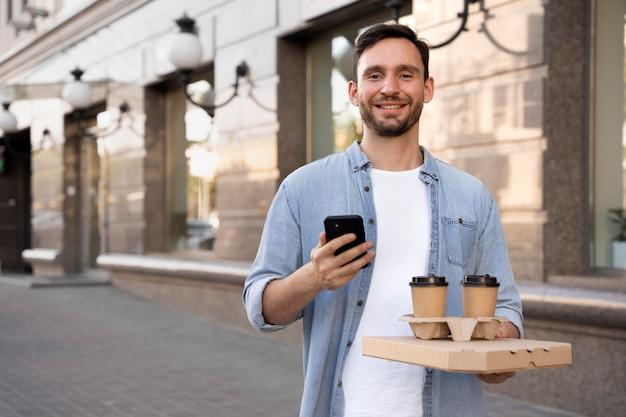 Uomo con cibo da asporto per strada usando lo smartphone