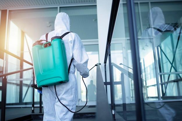 Uomo con il serbatoio del serbatoio sulla schiena spruzzando disinfettante per fermare il virus corona