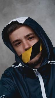 그의 입에 테이프를 가진 남자입니다. 입은 경고 테이프로 밀봉되어 있습니다.