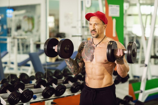 A man with a tattoo in a gym. execute exercise with dumbbells in colorful gym