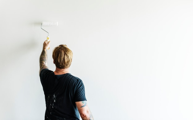 ローラーを保持している入れ墨を持つ男が壁を塗る