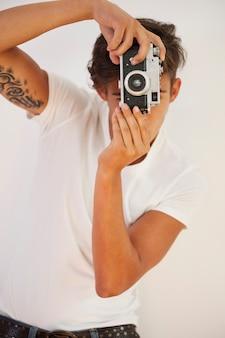 Man with tattoo taking photo by retro camera