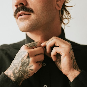 Man with tattooed hands buttoning his shirt.