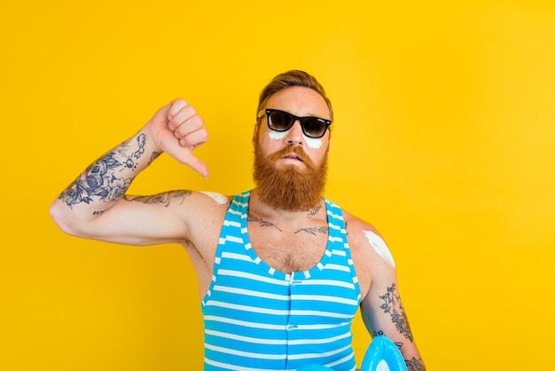 Мужчина с татуировками и купальником наносит солнцезащитный крем