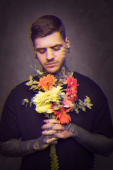 Man with tattoos holding a bouquet of flowers