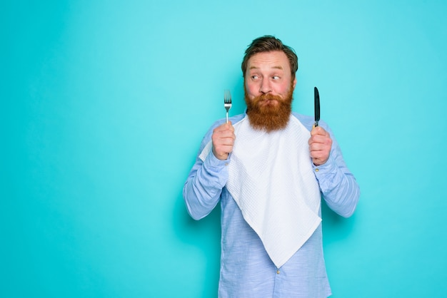 Man with tattoos is ready to eat with cutlery in hand