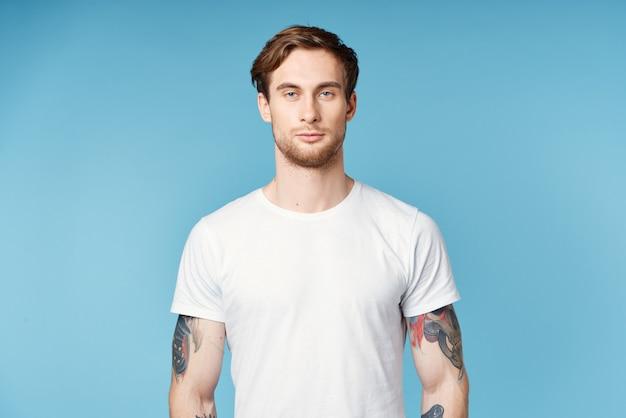 Человек с татуировками на руках белая футболка обрезанный вид на синем фоне