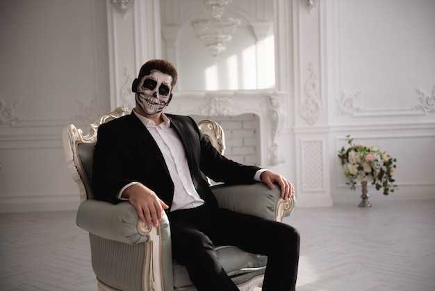 Man with a terrible make-up on white room background.