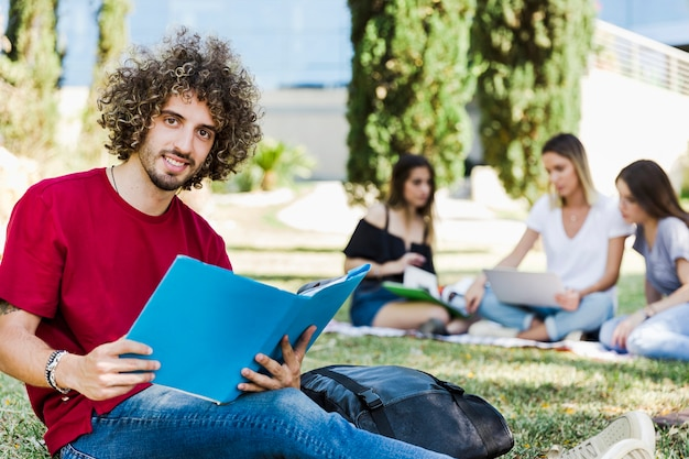 Man with textbook sitting on ground near friends