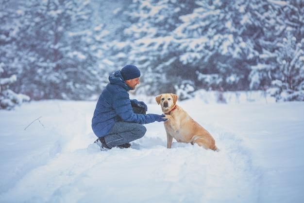Человек с собакой сидит в заснеженном сосновом лесу зимой
