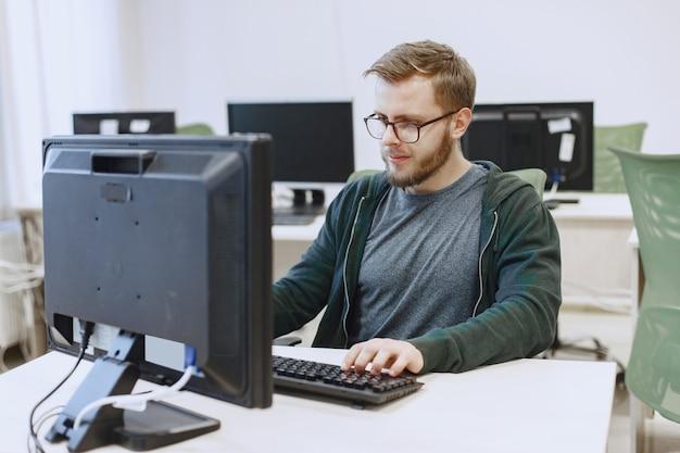 안경 남자. 컴퓨터 과학 수업의 학생. 사람은 컴퓨터를 사용합니다.
