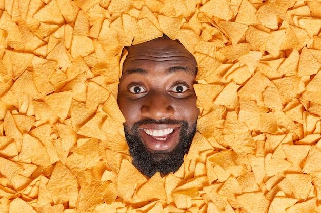 맛있는 멕시코 나초 칩에 묻힌 두꺼운 수염을 가진 남자는 맛있는 짠 매운 스낵을 활짝 웃는 것을 즐깁니다.