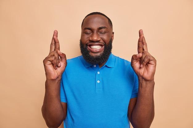 두꺼운 수염을 가진 남자는 행운을 빕니다를 믿으며 눈을 감고 베이지색에 캐주얼한 파란색 티셔츠를 입은 하얀 치아를 보여줍니다