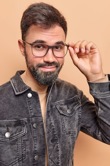 Man with thick beard looks directly at camera through glasses glad to have successful day dressed in black jacket poses indoor