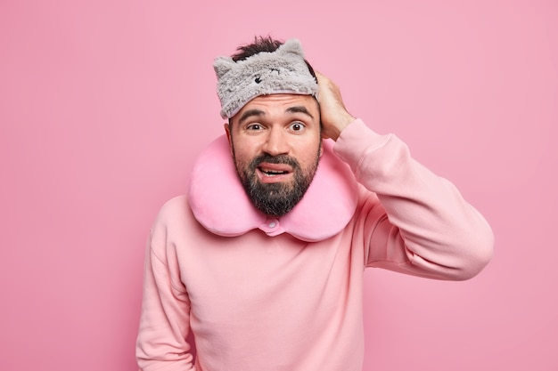 Man with thick beard scratches head frowns face wears sleepmask neck pillow dressed in casual jumper