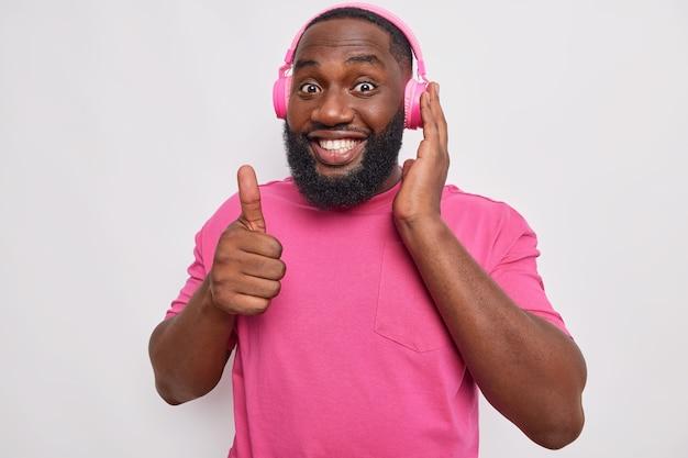 L'uomo con la barba folta sorride ampiamente mostra un segno eccellente tiene il pollice alzato ascolta musica in cuffie wireless indossa una maglietta rosa su bianco