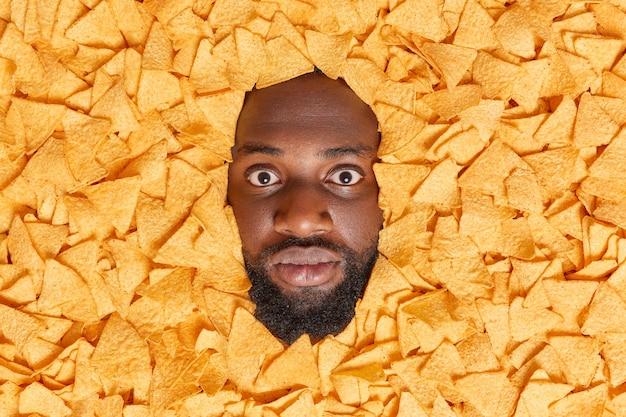 두꺼운 수염을 가진 남자는 바삭바삭한 칩에 둘러싸인 인상을 받고 건강에 해로운 간식을 먹고 많은 칼로리를 소비합니다