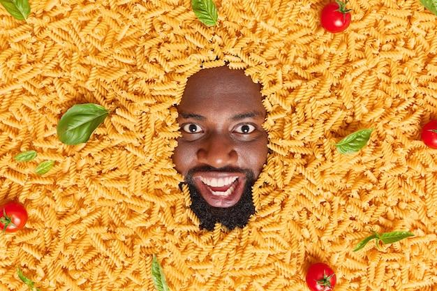 Man with thick beard sticks head in macaroni