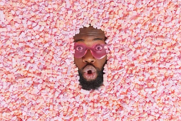 L'uomo con la barba folta si infila la testa attraverso deliziosi marshmallow mangia uno spuntino malsano ha dipendenza dallo zucchero indossa occhiali da sole alla moda ha un'espressione senza parole