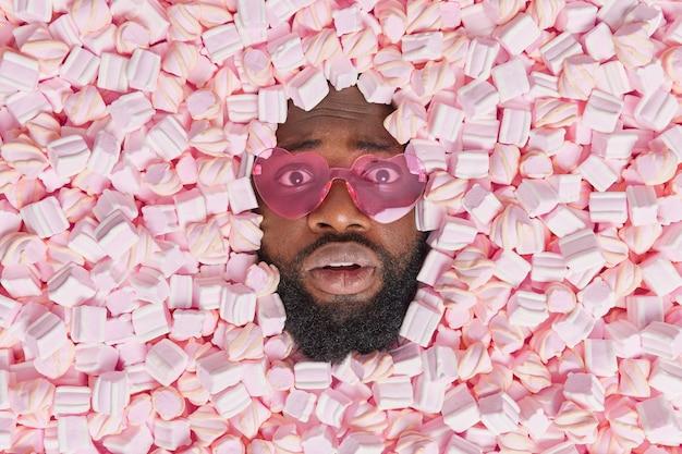 L'uomo con la barba folta indossa occhiali da sole alla moda a forma di cuore posa attraverso gustosi gusti marshmallow dessert essendo affamato pronto a mangiare tutte le prelibatezze