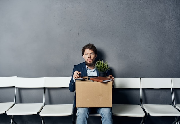 A man with things in a box sits on a chair waiting for discontent