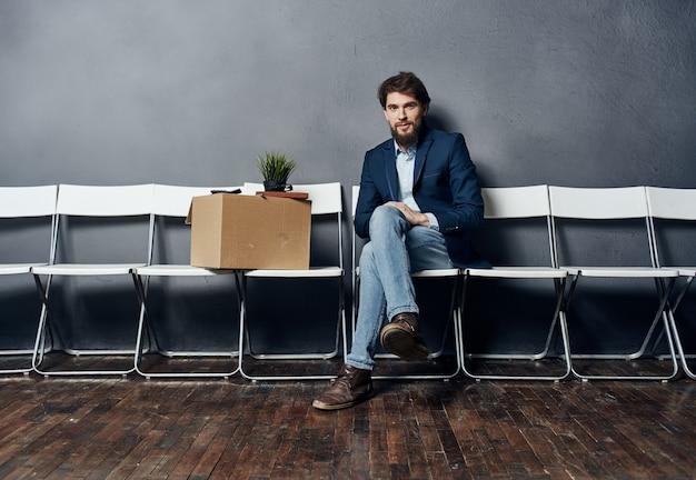 상자에 물건을 가진 남자는 불만을 기다리는 의자에 앉아