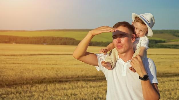 Мужчина с маленьким мальчиком в белой шляпе на плечах смотрит из-под руки на закатный свет летом на фоне сельского пейзажа с пшеничными полями