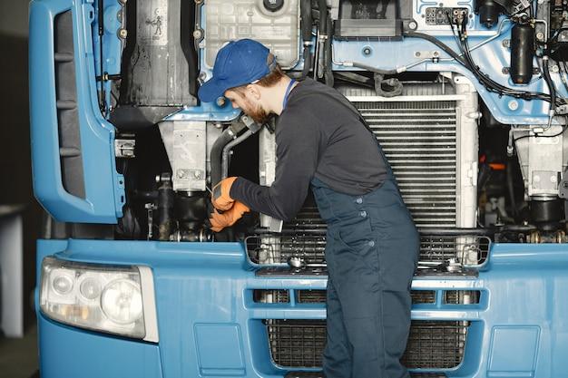 트럭 도구를 가진 남자입니다. 제복을 입은 노동자. 결함이있는 트럭