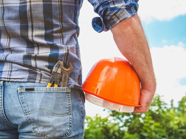 安全ヘルメットを保持しているツールを持つ男