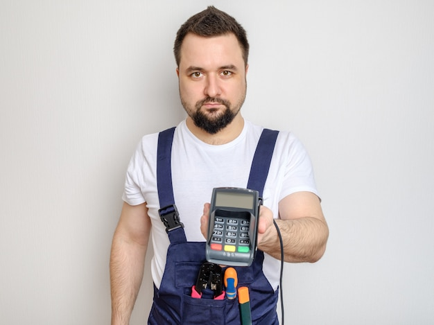 Man with tools holding bank payment terminal