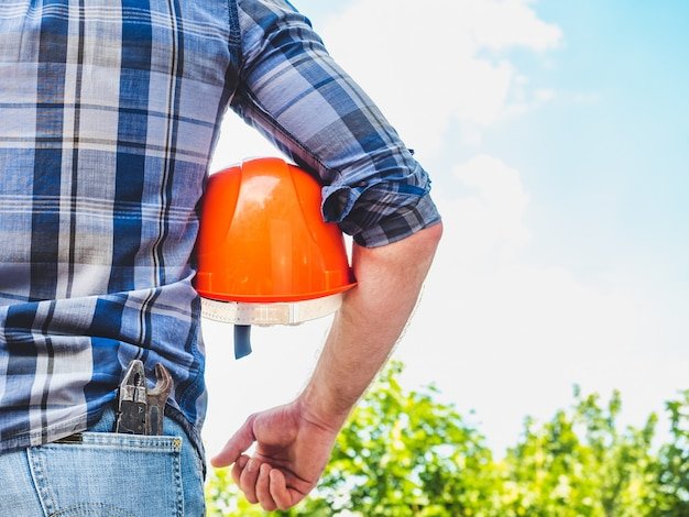 Man with tools holding a safety helmet