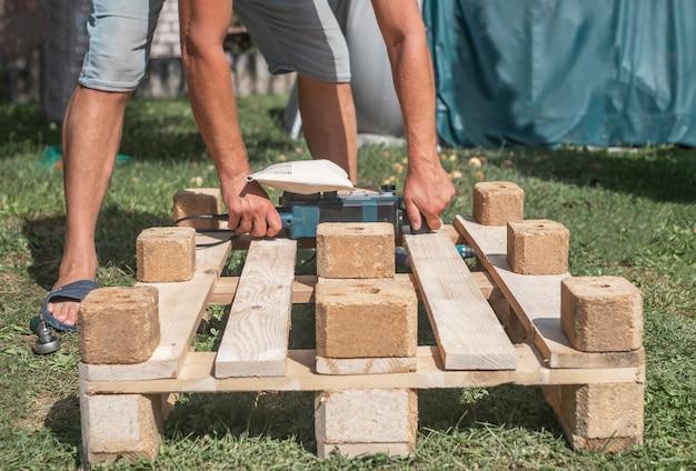 도구를 가진 남자는 자연에서 가구를 만들고 수리하는 나무 재료로 작업합니다.