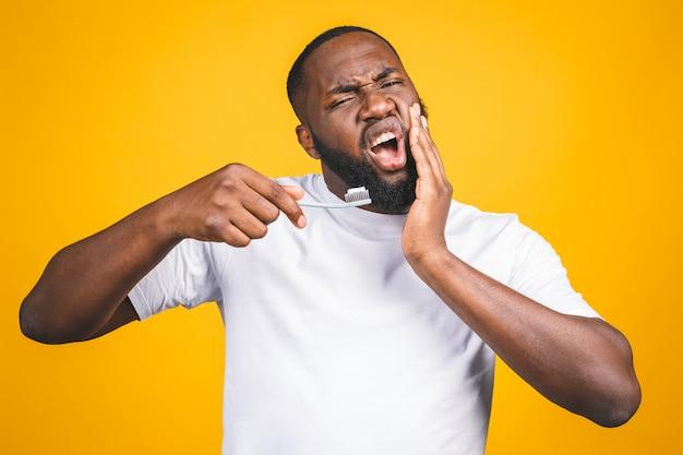 歯ブラシと歯痛を持つ男。歯磨き粉とリンゴと歯ブラシを保持している若い上半身裸のアフリカ人のイメージ